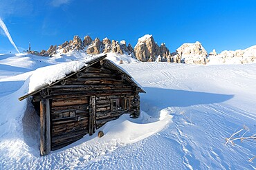 Isolated wooden hut covered with snow with Cir Group peaks in background at sunset, Passo Gardena, Dolomites, South Tyrol, Italy, Europe