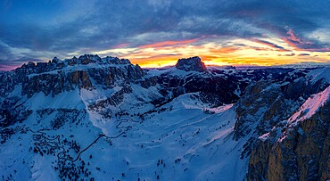 Clouds in the burning sky at sunset over Sassolungo and Sella Group mountains covered with snow, Dolomites, South Tyrol, Italy, Europe