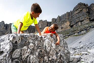 Smiling little boys looking at fossils on rocks, Orti della Regina, Brenta Dolomites, Madonna di Campiglio, Trentino, Italy, Europe