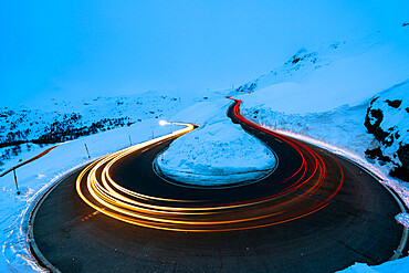 Car trail lights on bends of Bernina Pass road in winter, Val Poschiavo, canton of Graubunden, Engadin, Switzerland, Europe