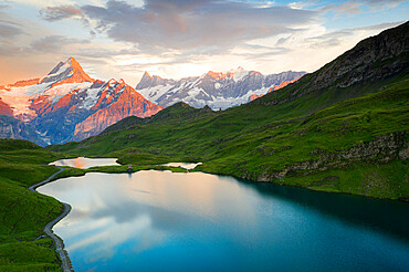 Schreckhorn and Finsteraarhorn peaks reflected in Bachalpsee lake at sunset, Grindelwald, Bernese Oberland, Switzerland