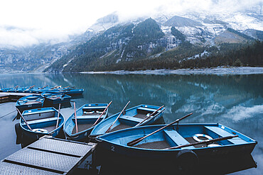 Row boats moored on shore of lake Oeschinensee on a foggy day, Bernese Oberland, Kandersteg, Bern canton, Switzerland