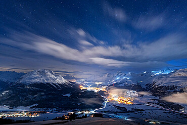 Starry winter sky over St. Moritz village and Upper Engadine covered with snow viewed from Muottas Muragl, Graubunden, Switzerland, Europe