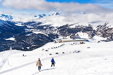 Two hikers walking on snowy slope towards the funicular station at Muottas Muragl, Samedan, Engadine, Graubunden, Switzerland, Europe