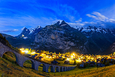 Steep viaduct of funicular above the illuminated village of Murren at night, Lauterbrunnen, Bernese Oberland, Switzerland