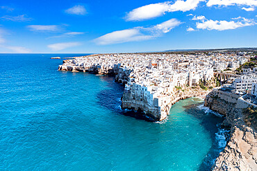 Aerial view of crystal sea surrounding Polignano a Mare on cliffs, province of Bari, Apulia, Italy