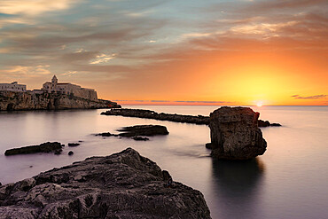 Clouds at sunrise over che calm sea surrounding Vieste, Foggia province, Gargano National Park, Apulia, Italy