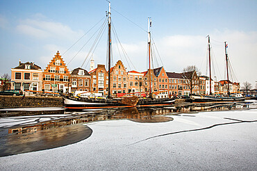 House facades and boats moored in the frozen canal of Spaarne river, Haarlem, Amsterdam district, North Holland, The Netherlands, Europe