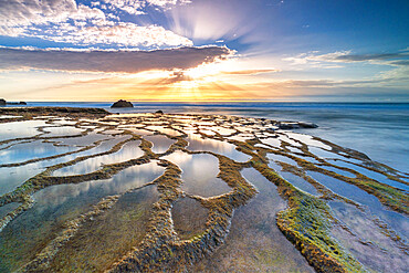 Natural pools and rocks in the surreal beach of El Cotillo lit by sunset, Fuerteventura, Canary Islands, Spain