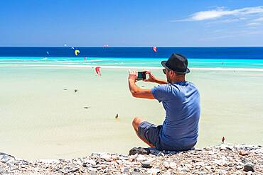 Tourist with straw hat photographing kiteboarders with smartphone at Sotavento beach, Jandia, Fuerteventura, Canary Islands, Spain