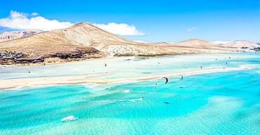 People kiteboarding on waves crashing on white sand of Sotavento beach, Jandia, Fuerteventura, Canary Islands, Spain