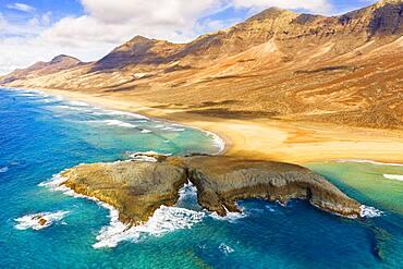 Aerial view of El Islote islet in the crystal ocean along Cofete beach, Jandia, Fuerteventura, Canary Islands, Spain