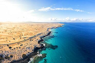 Aerial view of empty road beside the crystal turquoise ocean and sand dunes, Corralejo, Fuerteventura, Canary Islands, Spain, Atlantic, Europe