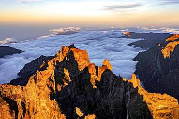 Clouds surrounding the rocky peak of Pico das Torres lit by sunset, Madeira island, Portugal, Atlantic, Europe