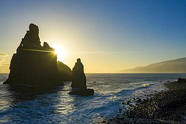Ilheus da Rib and Ribeira da Janela rock formations lit by sun rays at dawn, Atlantic Ocean, Porto Moniz, Madeira, Portugal
