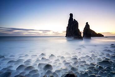 Long exposure of waves crashing on Ilheus da Rib and Ribeira da Janela rock formations at dusk, Madeira island, Portugal