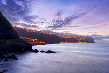 Dusk over the illuminated coastal village of Ponta do Sol, Madeira island, Portugal