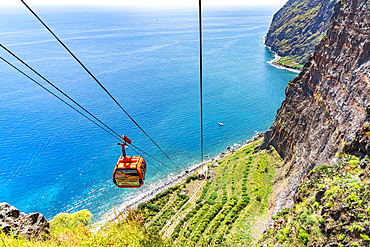 Elevated view of cable car Teleferico Do Rancho going down on steep crag to the ocean, Camara de Lobos, Madeira island, Portugal