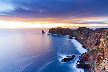 Dramatic sky at dawn on cliffs washed by ocean from Ponta Do Rosto viewpoint, Sao Lourenco Peninsula, Madeira, Portugal