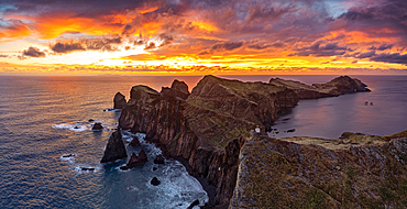 Cliffs by the ocean under the burning sky at dawn, Ponta Do Rosto, Sao Lourenco Peninsula, Madeira island, Portugal