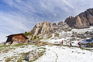 Hikers walking along the trail at the foot of the Sassolungo and Sassopiatto after a snowfall during springtime, Trentino-Alto Adige, Italy, Europe