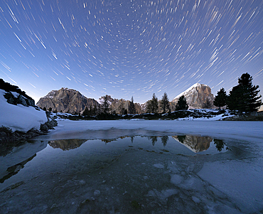 Polar star trail in the night sky over Lagazuoi and Tofana di Rozes peaks from frozen lake Limides, Dolomites, Veneto, Italy
