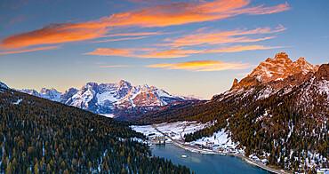 Sunrise over the snowy woods surrounding lake Misurina and Sorapis, aerial view, Dolomites, Belluno province, Veneto, Italy