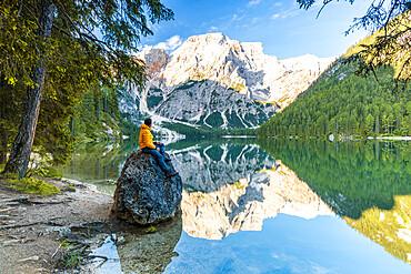 Hiker man enjoying sunrise sitting on rocks on shore of lake Braies / Pragser Wildsee at dawn, Dolomites, South Tyrol, Italy