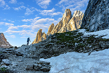 Hiker woman walking on path to majestic Croda Dei Toni mountain at dawn, Val Fiscalina, Sesto Dolomites, South Tyrol, Italy