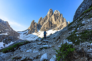 Hiker woman with backpack walking on path to Croda Dei Toni at sunrise, Val Fiscalina, Sesto Dolomites, South Tyrol, Italy