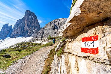 Rear view of hiker woman walking on path to majestic Croda Dei Toni mountain, Sesto Dolomites, South Tyrol, Italy