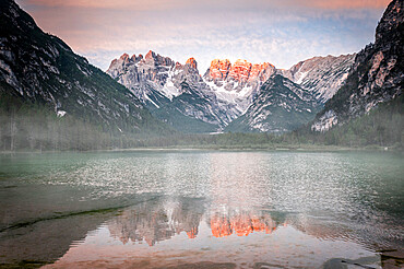 Popena group and Monte Cristallo mirrored in lake Landro (Durrensee) in the mist at dawn, Dolomites, South Tyrol, Italy