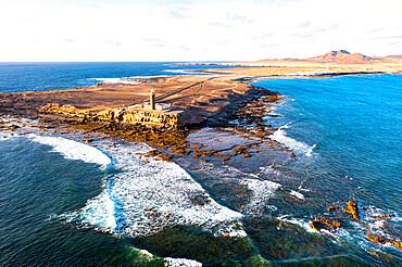 Sunset over the lighthouse of Punta Jandia (Faro de la Lola) washed by ocean waves, Fuerteventura, Canary Islands, Spain, Atlantic, Europe