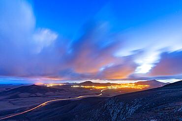 Car trail lights on desert road crossing the barren land at dusk, Vallebron lookout, Fuerteventura, Canary Islands, Spain, Atlantic, Europe
