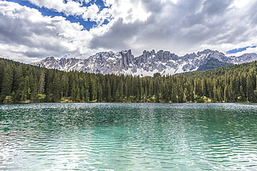 The still deep water of Lake Carezza surrounded by the picturesque frame of the Dolomites, in the Eggental in South Tyrol, Trentinto-Alto Adige, Italy, Europe