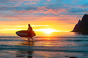Stand up paddle boarder man admiring midnight sun walking back to the beach, Ersfjord, Senja, Troms county, Norway