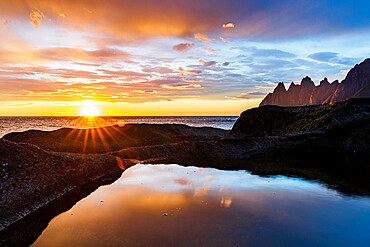 Midnight sun over the fjord and mountain peaks known as Devil's Teeth, Tungeneset viewpoint, Senja, Troms county, Norway