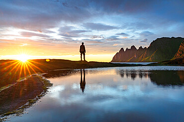 Silhouette of man standing on rocks watching the mountain peaks at sunset, Tungeneset viewpoint, Senja, Troms county, Norway