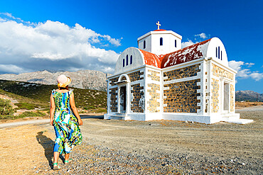 Rear view of woman with dress and straw hat walking to the Greek Orthodox church Agia Fotini, Pachia Ammos, Crete, Greece