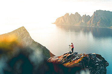Photographer with tripod on Husfjellet mountain watching sunset on sharp peaks of mount Okshornan (Devil's Teeth), Senja, Norway