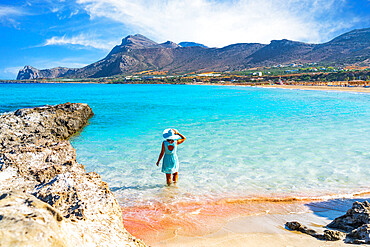 Beautiful woman with dress standing in the turquoise clear sea facing the pink sand beach of Falassarna, Crete, Greece