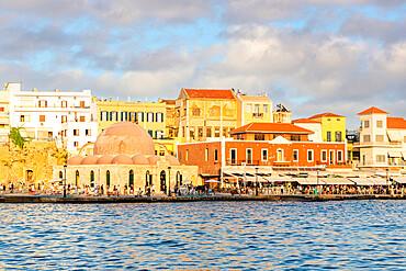 Tourists enjoying sunset at the old Venetian port of Chania, Crete, Greece