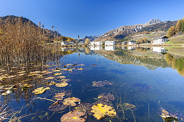 The little village of Tarasp in Low Engadine reflecting in a nearby pond, half covered in water lily leaves, Graubunden, Switzerland, Europe