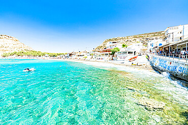 Beach of the seaside town resort of Matala washed by turquoise sea, Crete, Greece