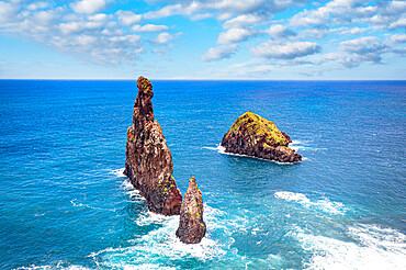 Aerial view of rock formation Ilheus da Rib and Ribeira da Janela in the rough ocean, Porto Moniz, Madeira island, Portugal