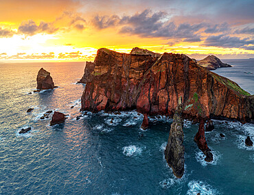 Burning sky at dawn on cliffs washed by ocean, Ponta do Rosto viewpoint, Sao Lourenco Peninsula, Madeira island, Portugal