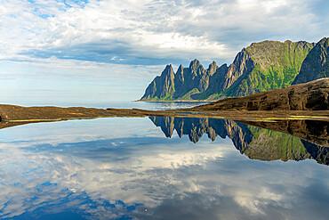 Cloudy sky over majestic rocks of mountain peaks mirrored in water, Tungeneset, Senja, Troms county, Norway