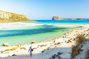 Tourists walking to the white sand beach surrounding Balos lagoon, Crete, Greece
