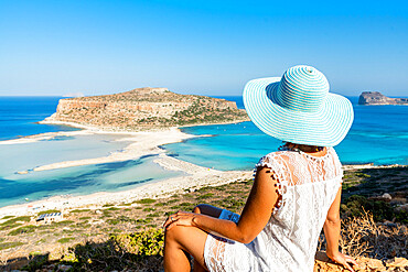 Portrait of beautiful woman with hat admiring the idyllic beach and lagoon sitting on top of mountain, Balos, Crete, Greece