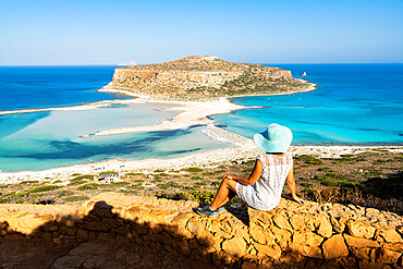 Charming woman with sundress and hat contemplating the crystal turquoise sea and lagoon, Balos, Crete, Greece